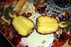 Не очищая ананас, разрезаем на две половинки.